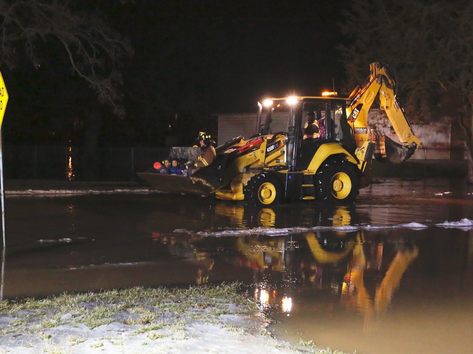 Kids are evacuated on a front end loader from a house along the river near South and Oak Street.