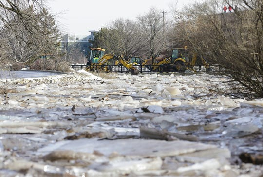 Fond du Lac Department of Public Works members use back hoes Thursday, March 14, 2019, to clear ice jams along the Fond du Lac River in Fond du Lac, Wis. Ice jams on the east branch of the Fond du Lac River caused localized flooding problems in the city.