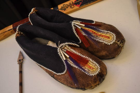 These replica Native American single-seam moccasins are decorated with beads and porcupine quills.