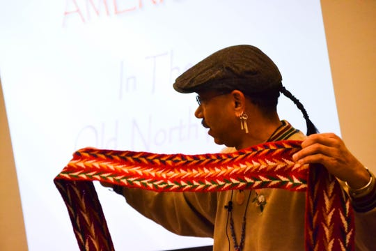 Jamie Oxendine shows the audience a sash he created using a finger weaving technique. Oxendine wears some of his handmade garments during reenactments and presentations.