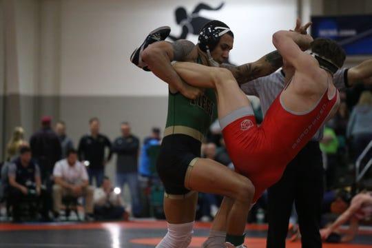 Ross graduate Trey Grine, left, takes down an opponent wrestling for Tiffin University.