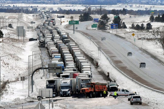 Trucks line I-25 south of Baptist Road on  Thursday, March 14, 2019 in Colorado Springs, Colo. A blizzard that paralyzed parts of Colorado and Wyoming barreled into the Midwest on Thursday, bringing whiteout conditions to western Nebraska and dumping heavy rain that prompted evacuations in communities farther east. (Jerilee Bennett)