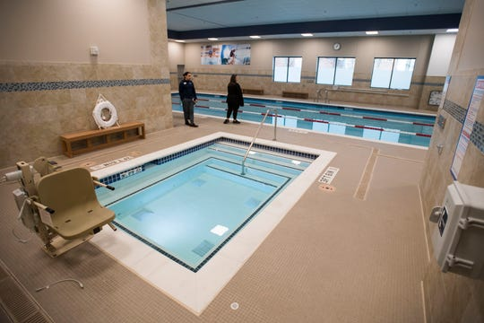 Regional fitness director Keita Pakawongse, left, and Shanda Keys give a tour of the swimming pool and hot tub on Thursday, March 14, 2019, at 24 Hour Fitness at the corner of East Mulberry Street and South College Avenue in Fort Collins, Colo.