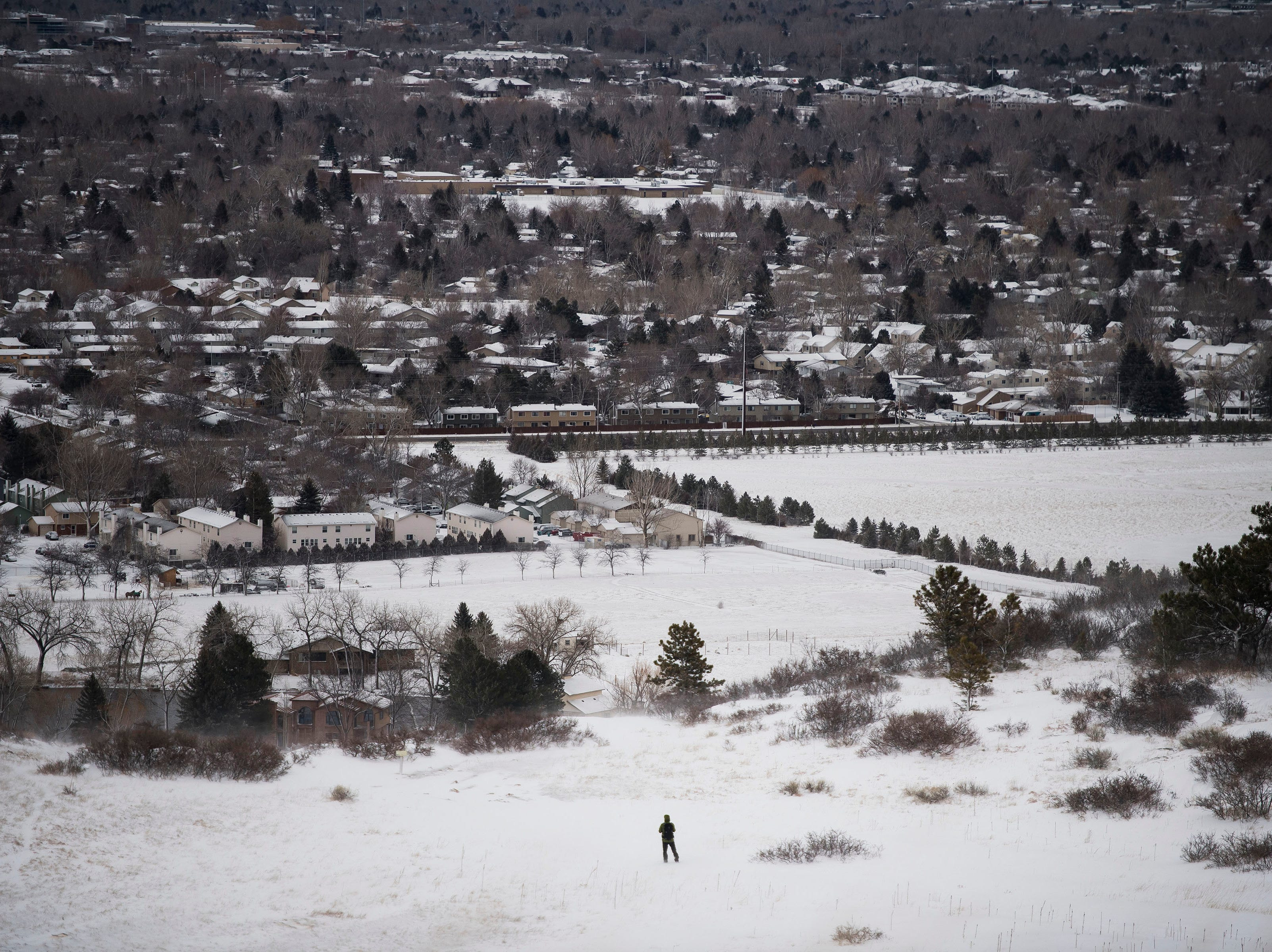 A hiker takes the Foothills Trail down from Horsetooth Reservoir to Maxwell Open Space during a break in the snowstorm on Wednesday, March 13, 2019, in Fort Collins, Colo.