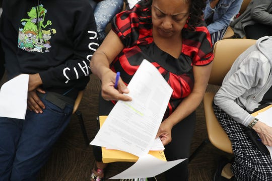 Sunrise Towers resident Julie Alexander looks over her housing voucher at a Fort Myers Housing Authority family briefing on Thursday 3/14/2019.