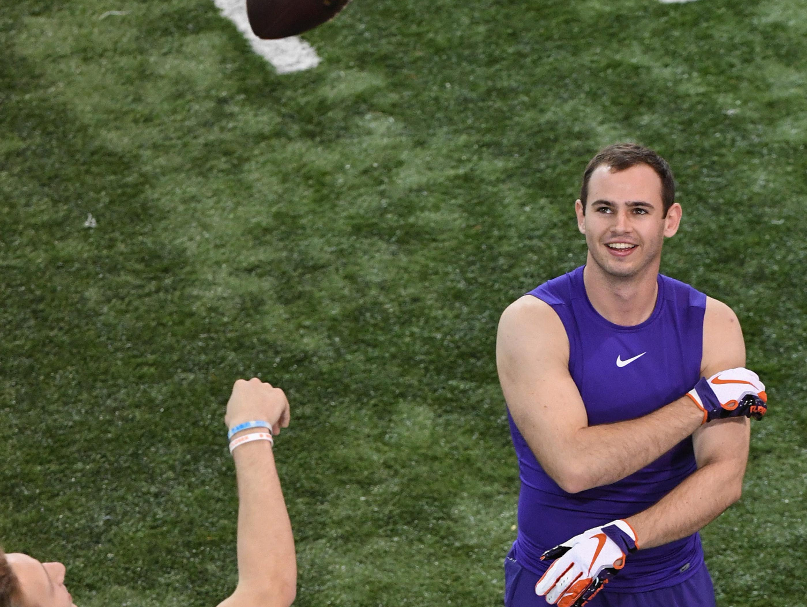 Clemson quarterback Trevor Lawrence tosses a ball around wide receiver Hunter Renfrow getting ready to be observed by pro scouts during Clemson pro day at the Poe Indoor Facility in Clemson Thursday, March 14, 2019.
