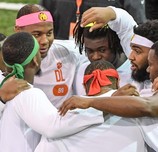 Defensive players Clelin Ferrell, left, Dexter Lawrence, Albert Huggins, Austin Bryant and Christian Wilkins, wearing headbands through drills and tests as Power Rangers, huddle during Clemson pro day at the Poe Indoor Facility in Clemson Thursday, March 14, 2019.
