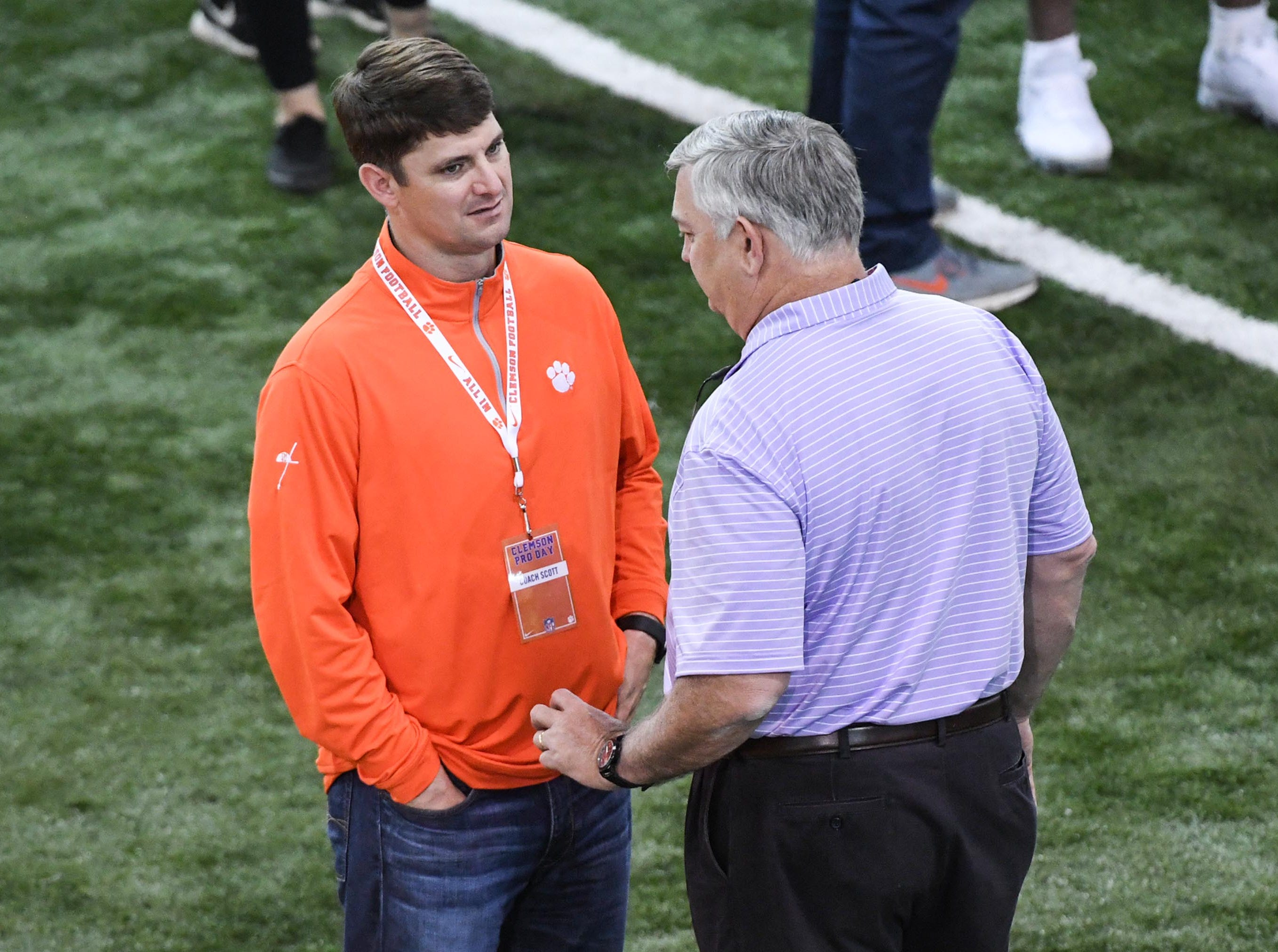 Clemson offensive coordinator Jeff Scott talks with his father Brad Scott, right, during Clemson pro day at the Poe Indoor Facility in Clemson Thursday, March 14, 2019.