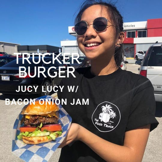 "A Food Truck employee holds one of mobile restaurant's signature ""Juicy Lucy"" burgers. The Food Truck owner Joey Atalig helped organize the Food Truck Frenzy weekly gatherings at Pago Bay and Skinner Plaza."