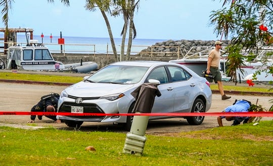 Guam Police Department officers search the underside of a vehicle parked in the vicinity of the Guam Fire Department Rescue Base 2, after Route 2 was reopened to traveling motorists on Tuesday, March 12, 2019. The section of roadway, which runs in front of the Agat Marina parking lot, was closed to drivers for several hours as local and federal emergency personel responded to a suspicious device discovered just outside the rescue base. The device, was later determined to be a training device, used by GFD for instructional purposes, according to GFD.