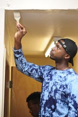 Logistics Specialist Second Class Prince Angelo paints during a community service event on March 9 at Safe Haven Pregnancy Center in Asan.
