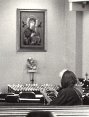 In this 1984 file photo, a lone woman prays before a picture of Our Lady of Perpetual Help at the Agana Cathedral.