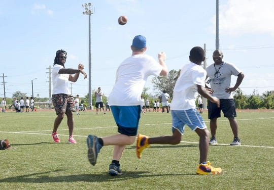 Jaylon Smith, a linebacker for the Dallas Cowboys, throws a pass to kids while running drills during the Jaylon Smith Football Pro Camp at Blue Jacket Field on March 10.
