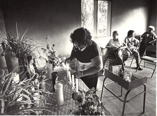 Mary Camacho lights candles at the old Santa Cruz chapel in Yona prior to the start of a novena in honor of the saint in this 1983 file photo.