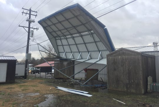 A commercial-sized carport roof was blown onto power lines Thursday afternoon at Eagle Buildings in Waverly. Kentucky Utilities was on-site dealing with the problem while the wind and rain were still blowing.