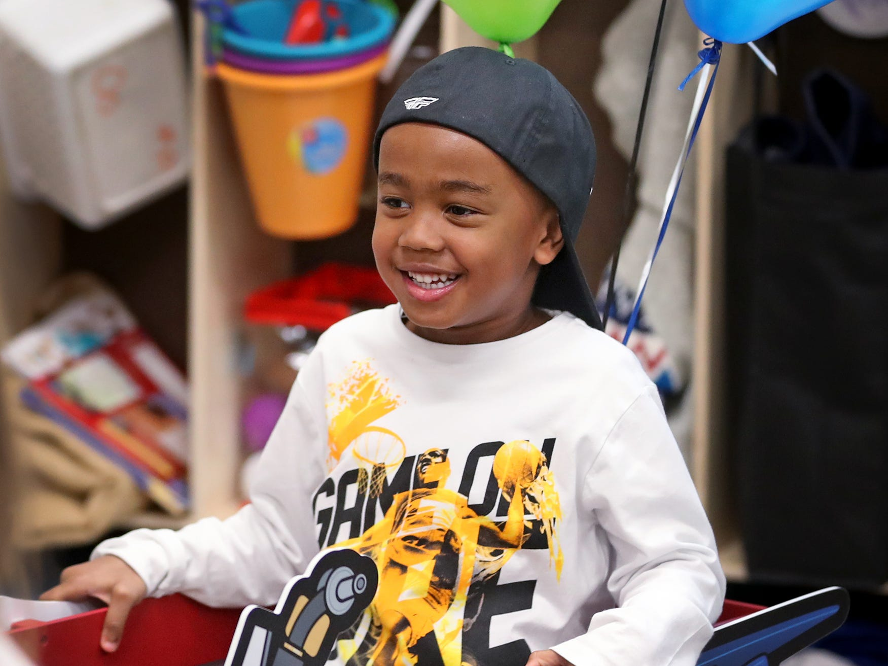 Dycen Tyler laughs while getting a wagon ride from Supercross racer Mike Alessi visiting with kids at Day Early Learning Center, Thursday, March 14, 2019.  Alessi provided Supercross rider jerseys and hats for the kids and gave wagon rides, on a break before the upcoming Supercross race.
