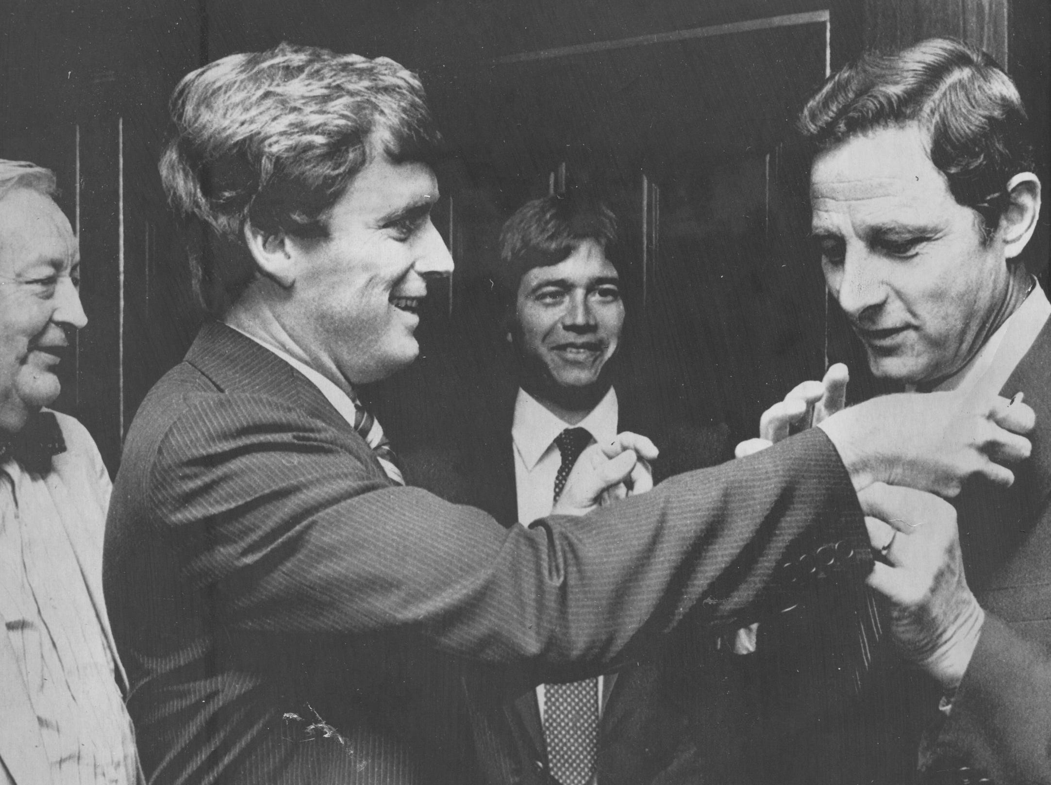 Merrillville, Ind. June 2, 1980: Meeting in hallway between their separate presentations to the AP Managing Editors at Convention in Merrillville, Dan Quayle sticks his campaign label on Birch Bayh's lapel. It did not stay there long.
