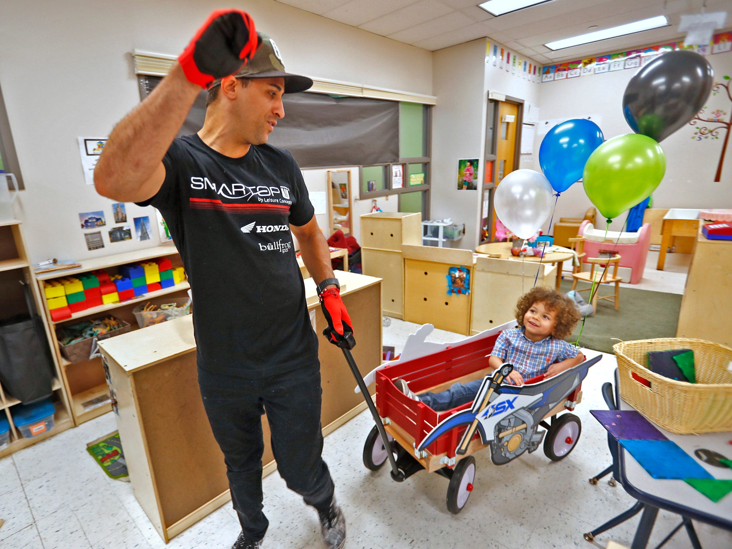 Dominic Bailey laughs while getting a wagon ride from Supercross racer Mike Alessi visiting with kids at Day Early Learning Center, Thursday, March 14, 2019.  Alessi provided Supercross rider jerseys and hats for the kids and gave wagon rides, on a break before the upcoming Supercross race.