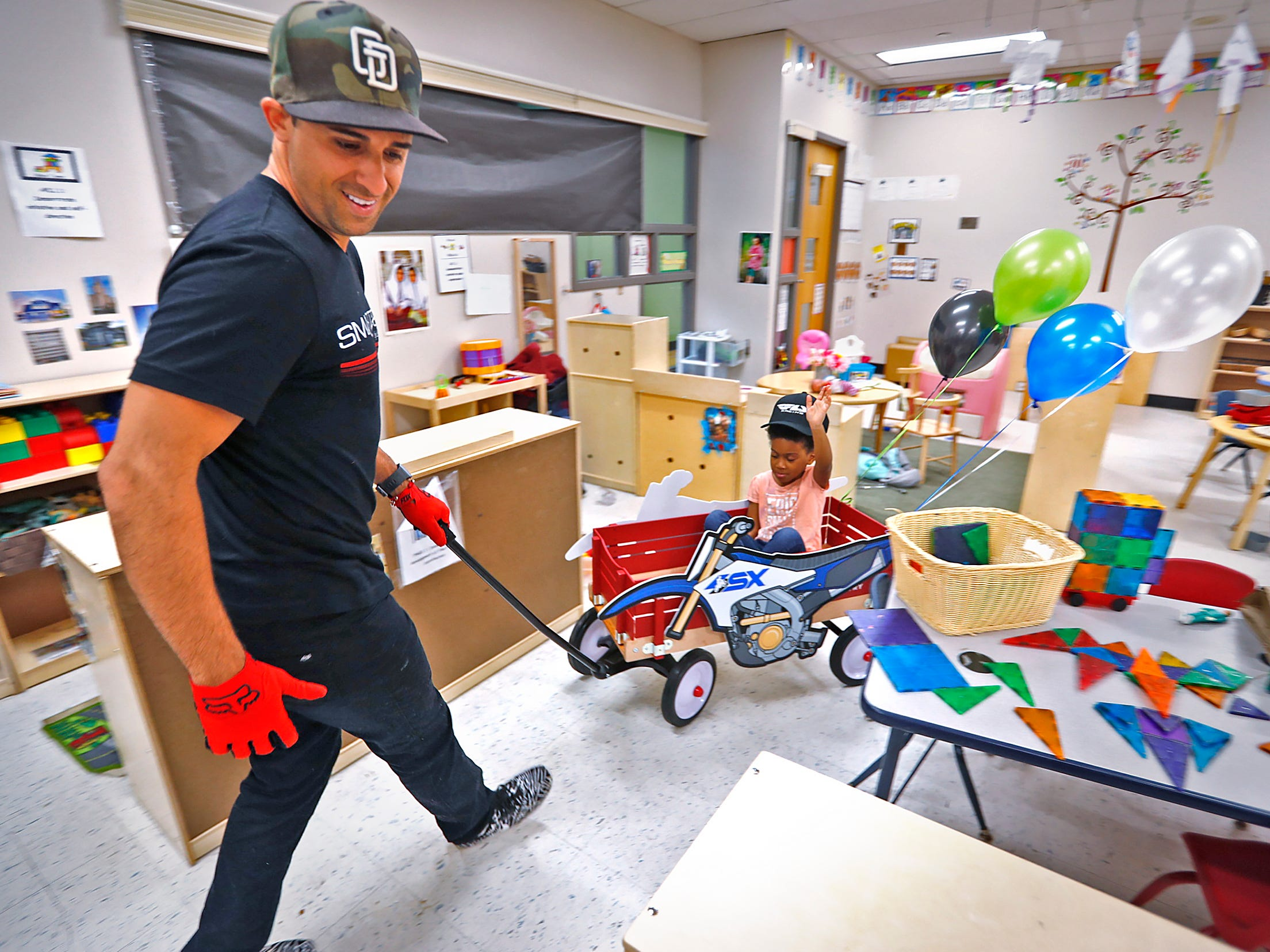 Roselynn Arnold puts her hands up while getting a wagon ride from Supercross racer Mike Alessi visiting with kids at Day Early Learning Center, Thursday, March 14, 2019.  Alessi provided Supercross rider jerseys and hats for the kids and gave wagon rides, on a break before the upcoming Supercross race.