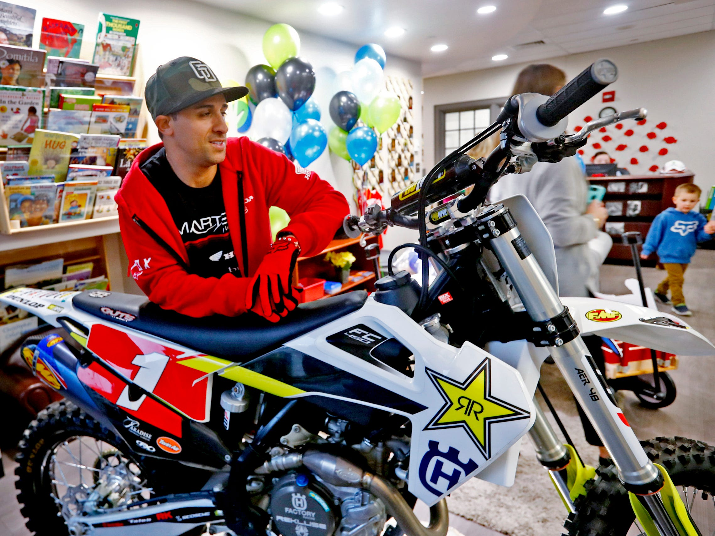 Supercross racer Mike Alessi leans on a bike simulator as he visits with kids at Day Early Learning Center, Thursday, March 14, 2019.  Alessi provided Supercross rider jerseys and hats for the kids and gave wagon rides, on a break before the upcoming Supercross race.