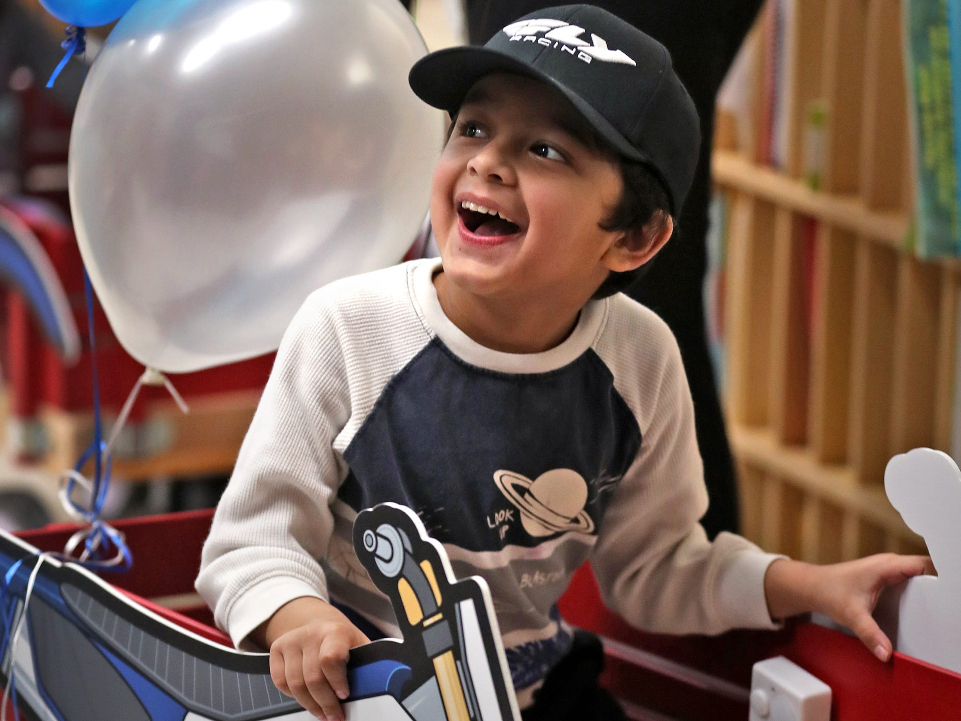 Abhiraj Singh laughs while getting a wagon ride from Supercross racer Mike Alessi visiting with kids at Day Early Learning Center, Thursday, March 14, 2019.  Alessi provided Supercross rider jerseys and hats for the kids and gave wagon rides, on a break before the upcoming Supercross race.