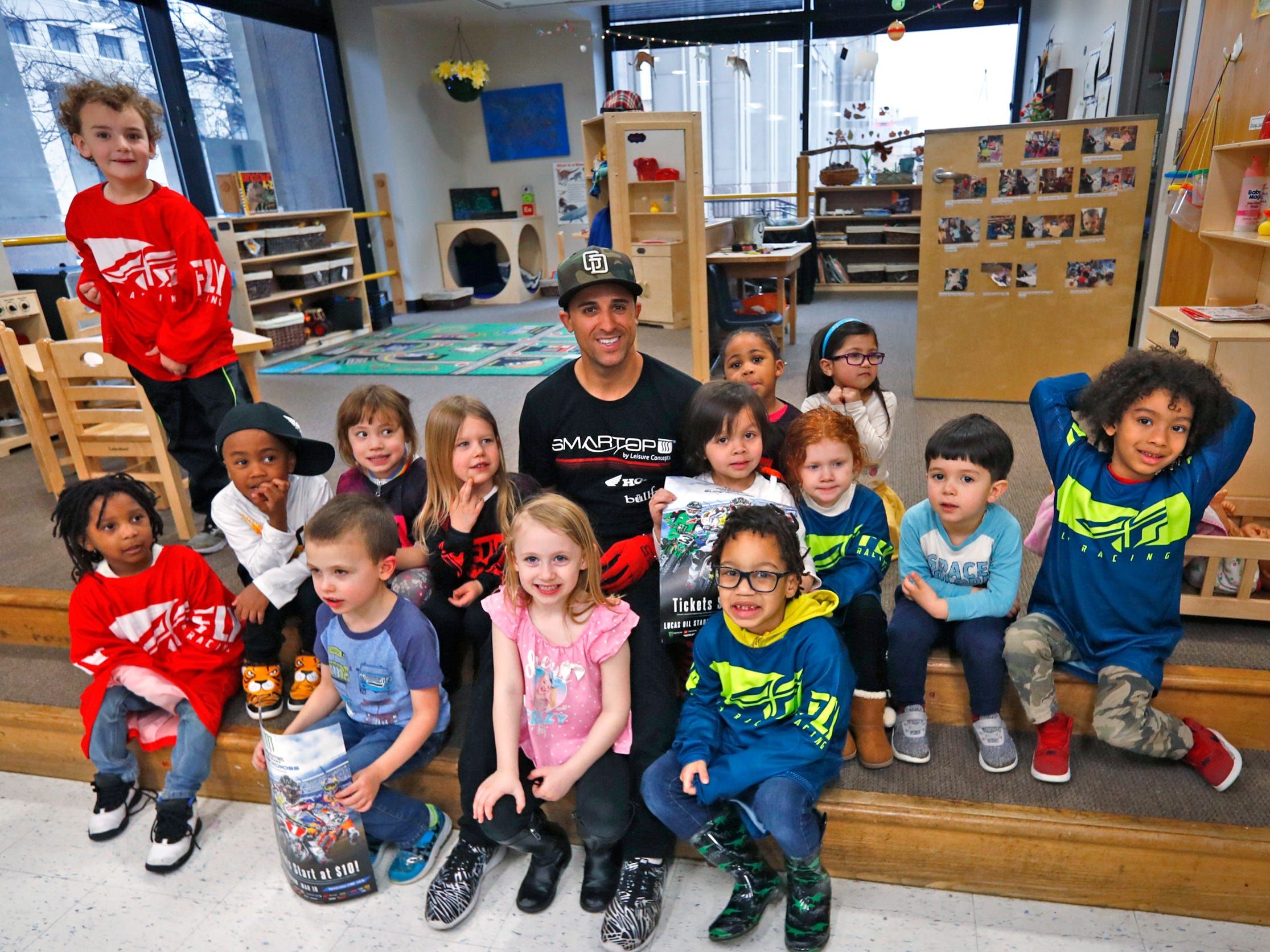 Supercross racer Mike Alessi poses for a photo as he visits with kids at Day Early Learning Center, Thursday, March 14, 2019.  Alessi provided Supercross rider jerseys and hats for the kids and gave wagon rides, on a break before the upcoming Supercross race.
