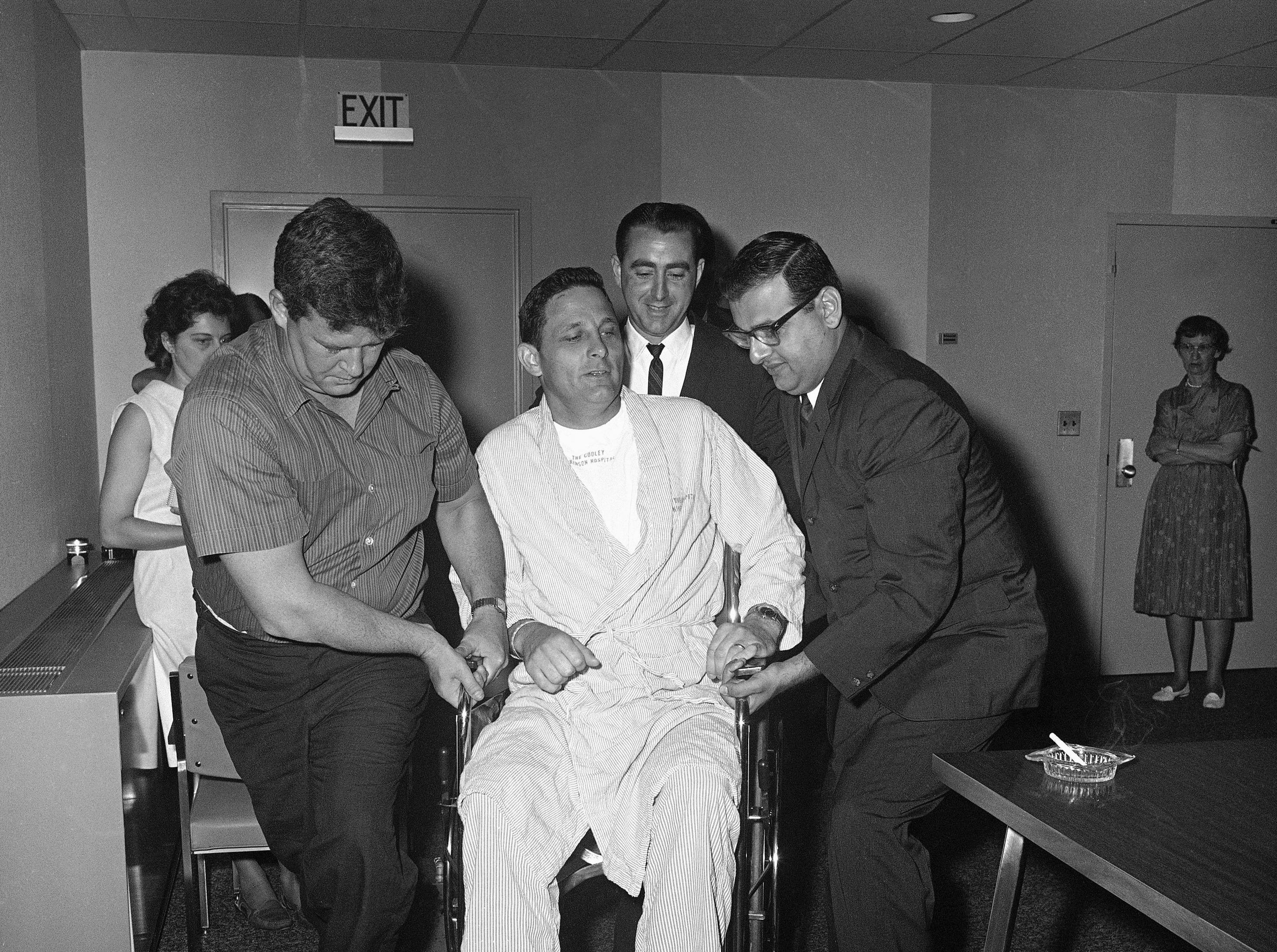 Senator Birch Bayh of Indiana, injured in airplane accident last week, is lifted in his wheelchair to stage of Cooley Dickinson Hospital to talk with press, June 24, 1964 in Northampton. Two persons were killed in the accident and Senator Edward Kennedy seriously injured. (AP Photo)