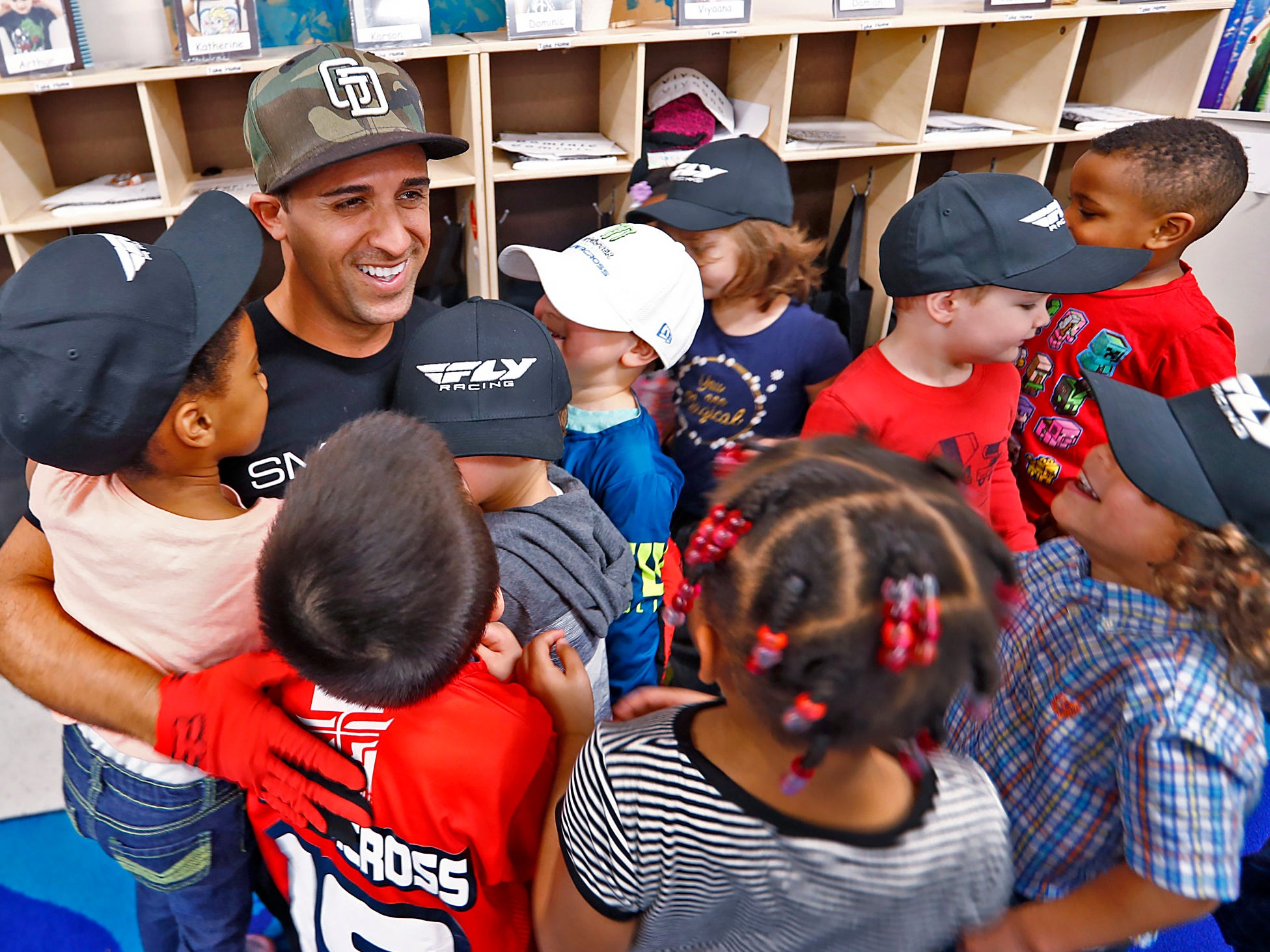 Supercross racer Mike Alessi laughs while getting a group hug as he visitswith kids at Day Early Learning Center, Thursday, March 14, 2019.  Alessi provided Supercross rider jerseys and hats for the kids and gave wagon rides, on a break before the upcoming Supercross race.