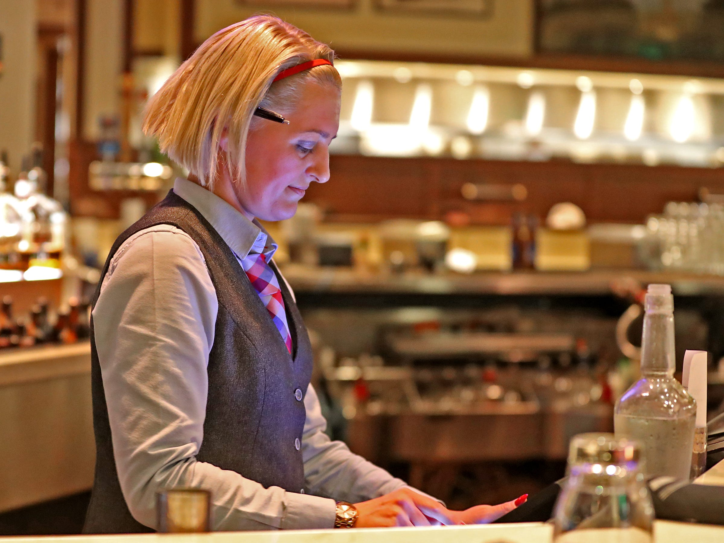 Roxanne Green tallies up a bill while working at Burger Study, Thursday, March 14, 2019.  The restaurant uses Snapshyft to help supplement their staffing during peak times.