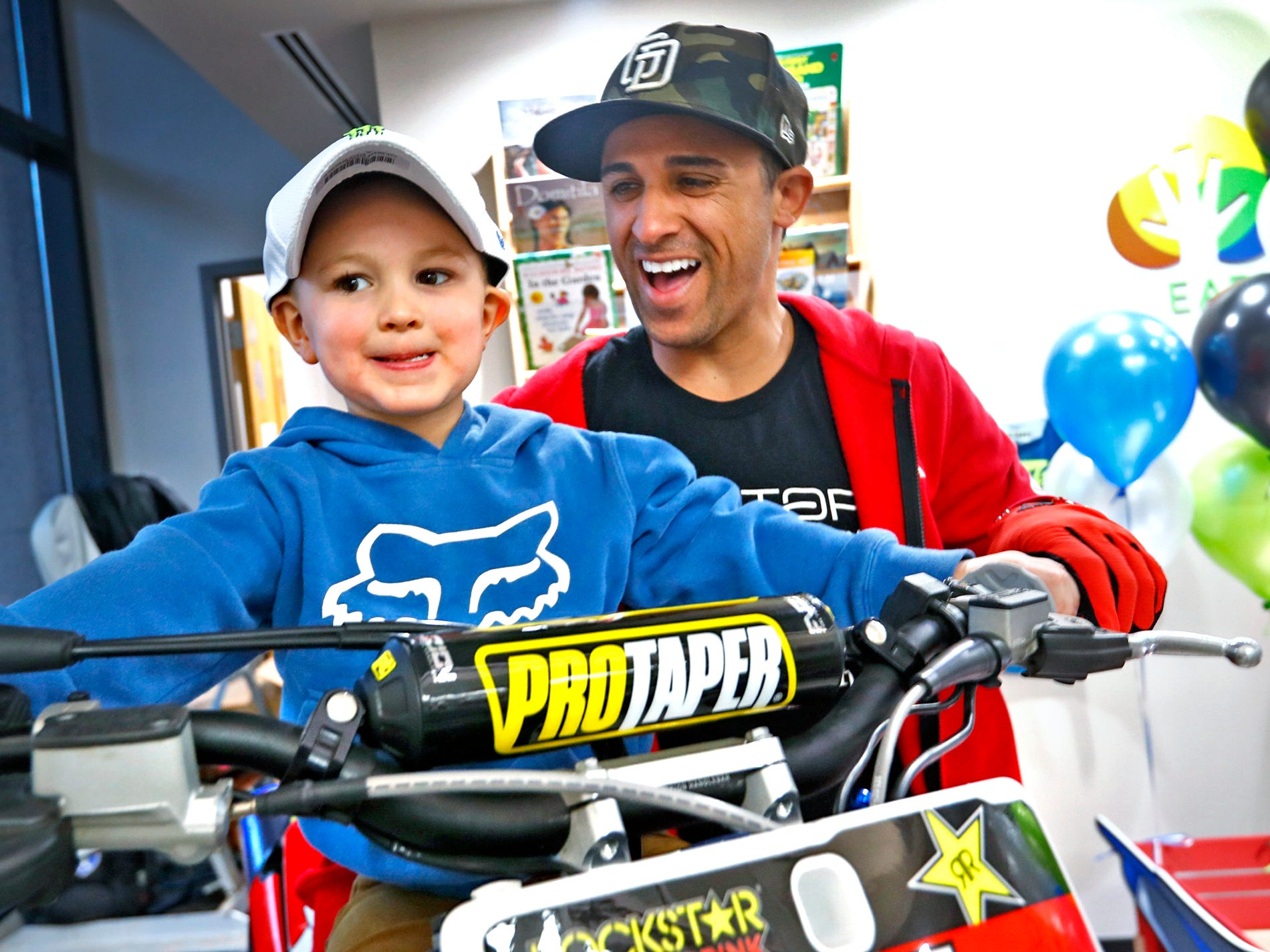 Supercross racer Mike Alessi, right, laughs with Jaxson Bare trying out a Superercross simulator, as Alessi visits with kids at Day Early Learning Center, Thursday, March 14, 2019.  Alessi provided Supercross rider jerseys and hats for the kids and gave wagon rides, on a break before the upcoming Supercross race.
