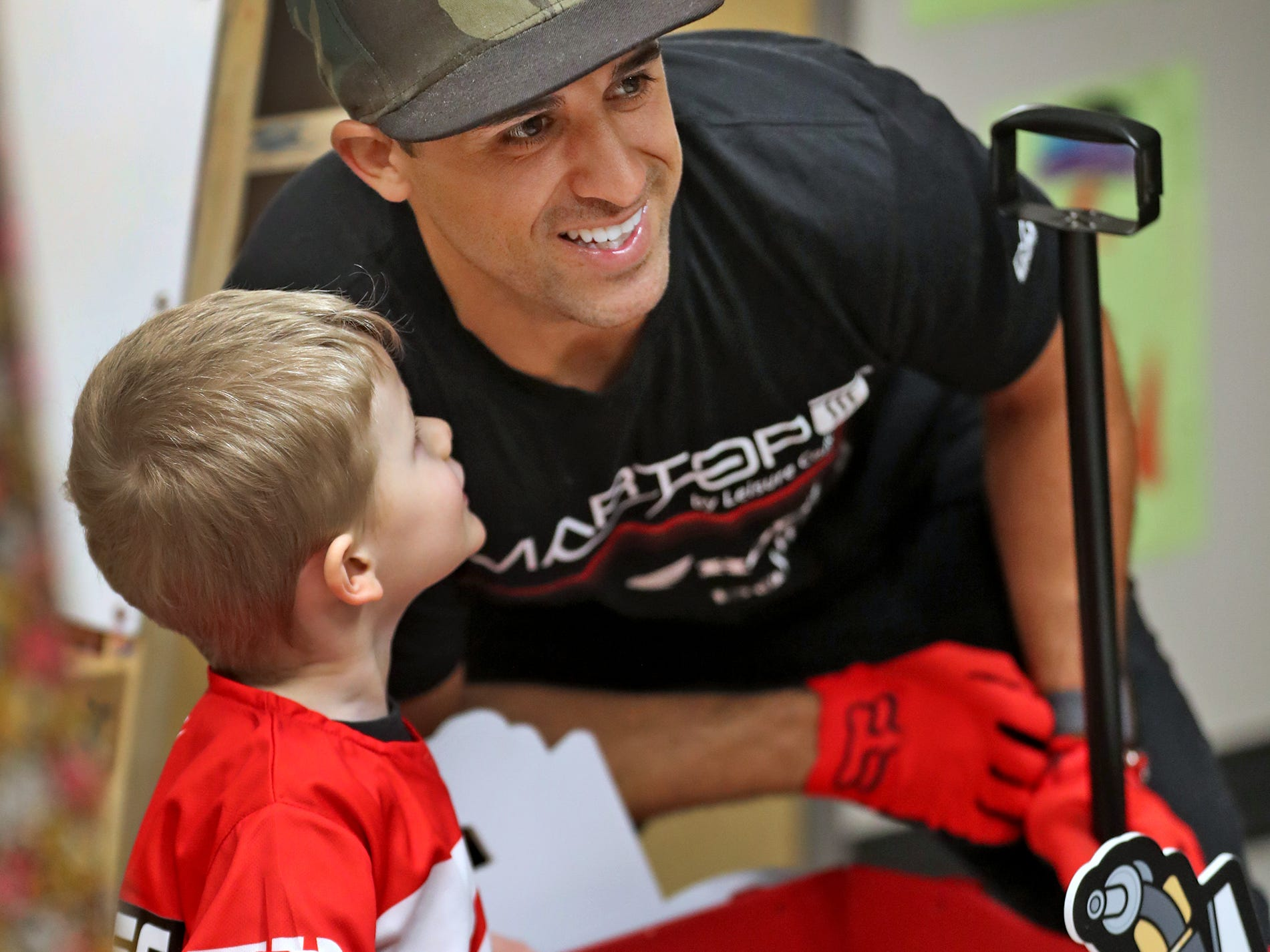 Oliver Carleton, left, looks up as he gets a photo taken with  Supercross racer Mike Alessi visiting with kids at Day Early Learning Center, Thursday, March 14, 2019.  Alessi provided Supercross rider jerseys and hats for the kids and gave wagon rides, on a break before the upcoming Supercross race.