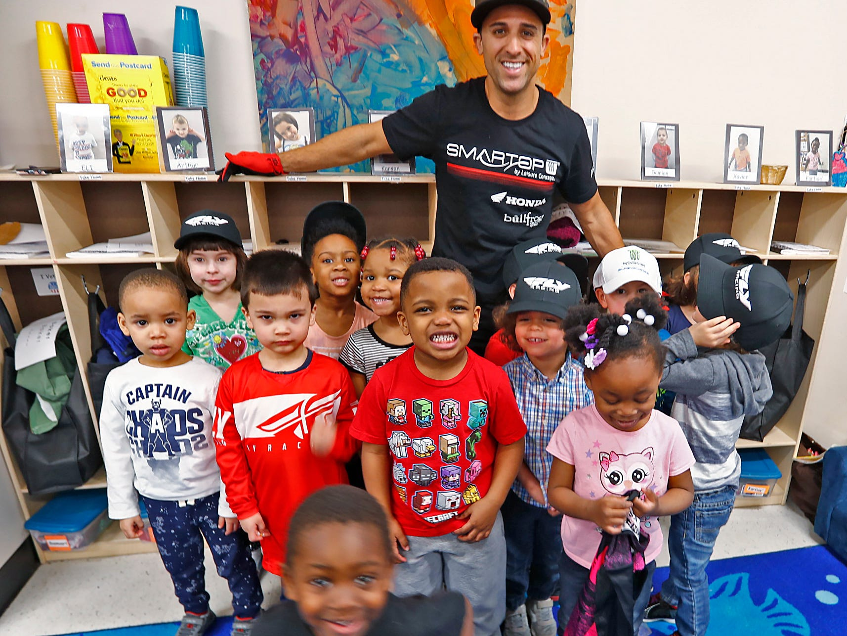 Supercross racer Mike Alessi poses for a photo while visiting with kids at Day Early Learning Center, Thursday, March 14, 2019.  Alessi provided Supercross rider jerseys and hats for the kids and gave wagon rides, on a break before the upcoming Supercross race.