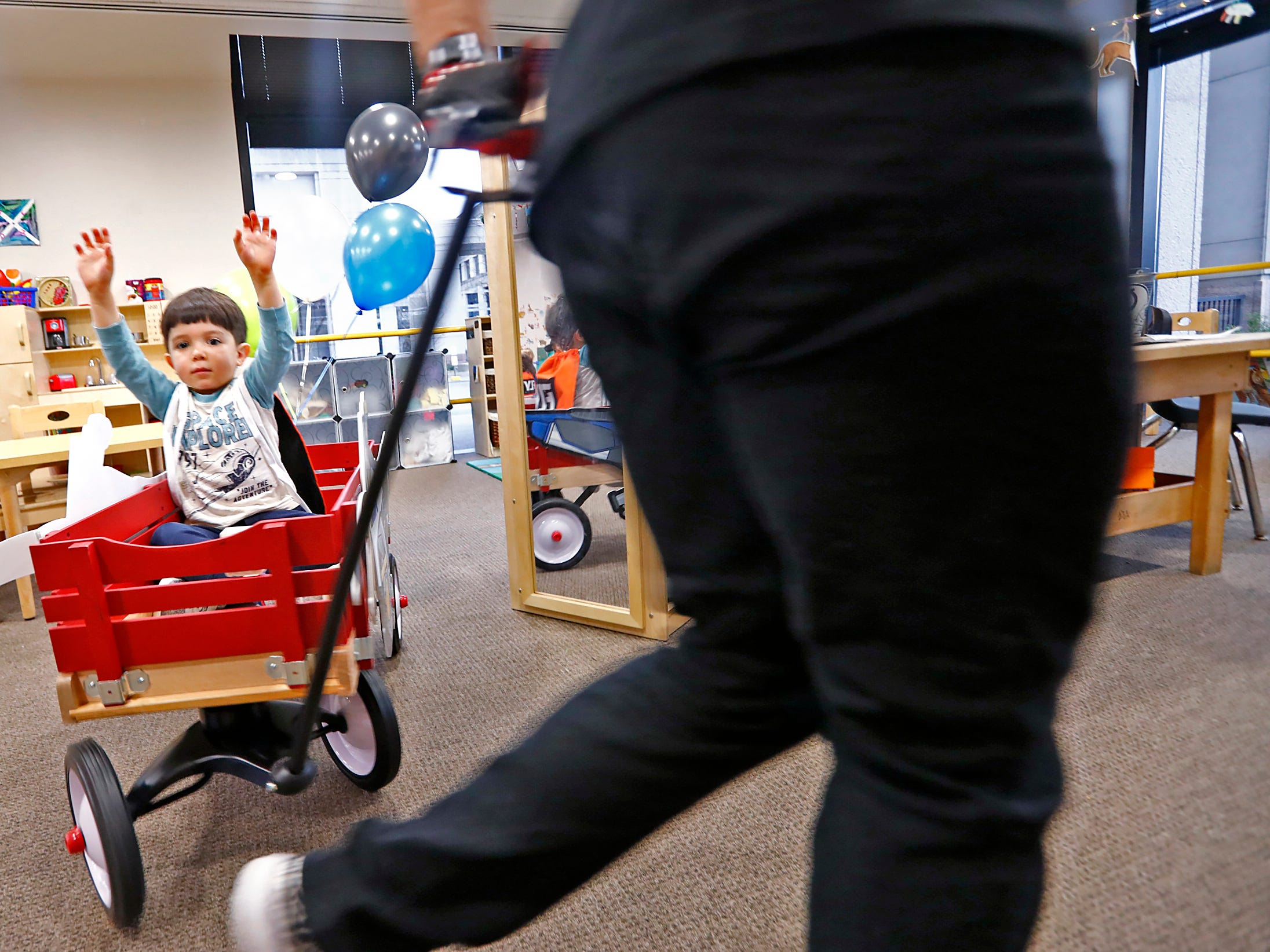 Adam Gayed puts his hands up as he get a wagon ride from Supercross racer Mike Alessi visiting with kids at Day Early Learning Center, Thursday, March 14, 2019.  Alessi provided Supercross rider jerseys and hats for the kids and gave wagon rides, on a break before the upcoming Supercross race.