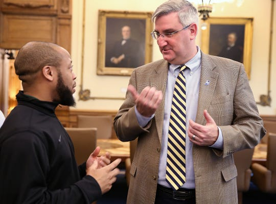 Crispus Attucks coach Chris Hawkins (left) speaks with Indiana Governor Eric Holcomb in his office, as the team was honored for winning the 2017 Class 3A state title.