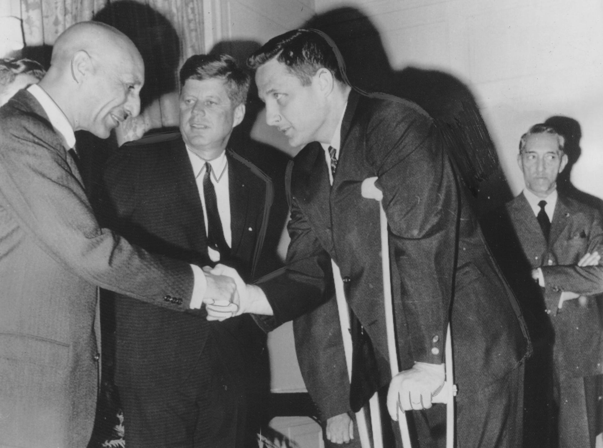 King Mohammed Zahir Shah of Afghanistan, shaking hands with Senator Birch Bayh (D-Ind.) at a luncheon yesterday at the Afghanistan Embassy in Washington. President John F. Kennedy, honor guest at the affair, stands next to the visiting monarch. Senator Bayh has been getting around on crutches because of an amputated toe which was mangled in a lawn mower accident. (09/07/1963)