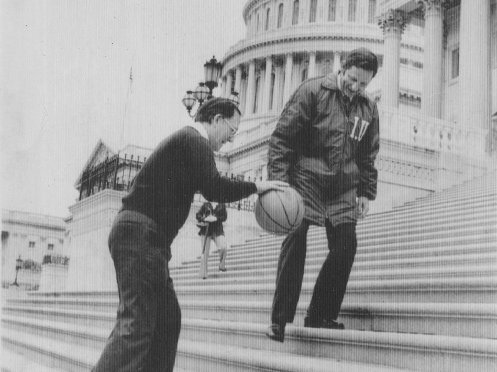 Washington: Indiana Sen. Birch Bayh watches MIchigan Sen. Robert Griffin dribble a basketball all up the steps of the U.S. Capitol on March 30, 1976. Griffin was paying off a bit--he picked the Wolverines to beat the Hoosiers in the NCAA final the following evening. As every sport buff knows, Indiana won, 86-88.