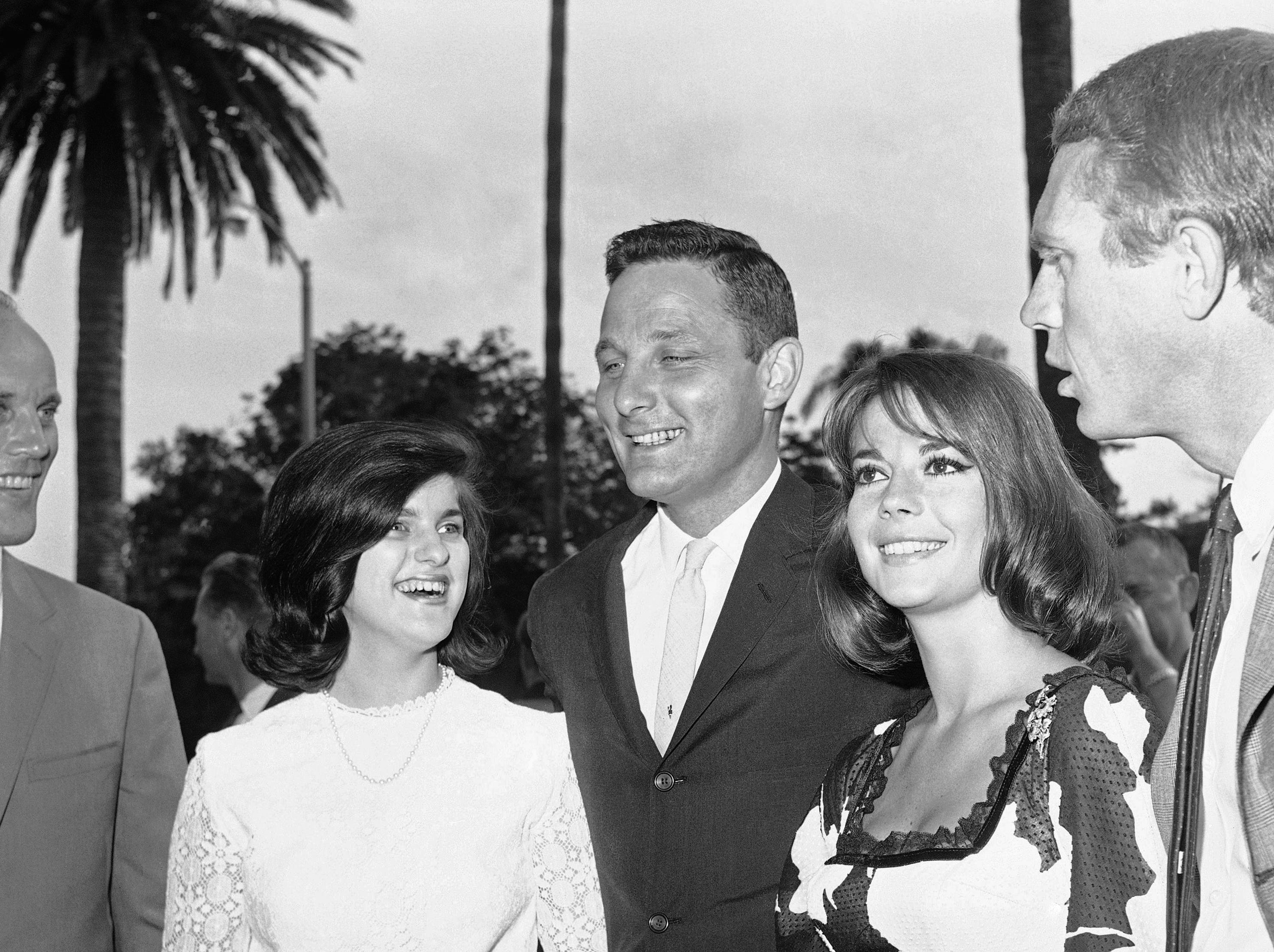 Luci Baines Johnson, younger daughter of President Johnson (left) and Indiana Sen. Birch Bayh arrive for Young Citizens for Johnson Texas-style barbecue at Beverly Hills, August 9, 1964. Welcoming them are co-sponsors actress Natalie Wood and actor Steve McQueen. Over one thousand persons attended the affair. (AP Photo/Harold Matosian)