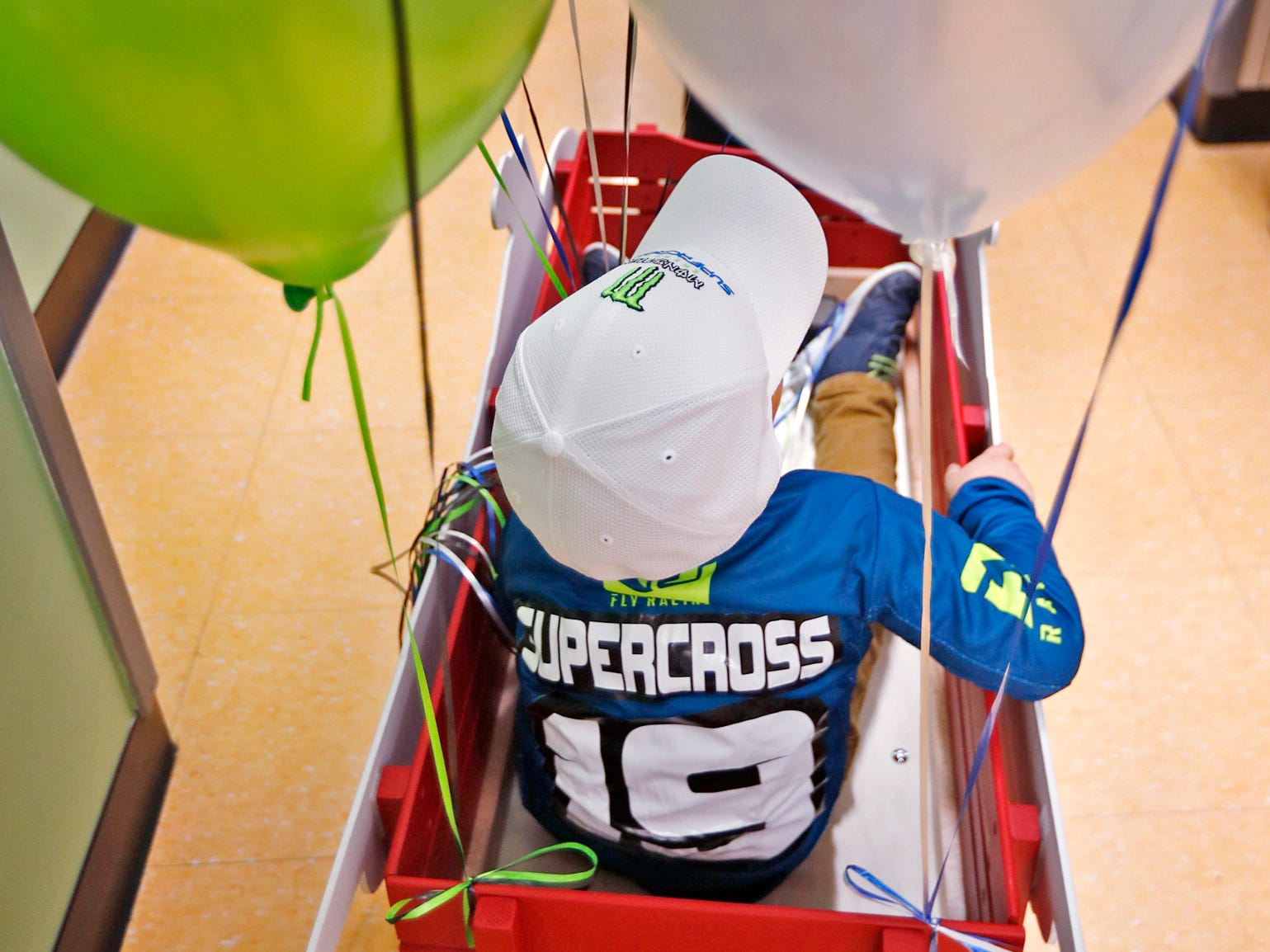 Jaxson Bare rides in a wagon to classrooms at Day Early Learning Center with Supercross racer Mike Alessi who visits with kids at the center, Thursday, March 14, 2019.  Alessi provided Supercross rider jerseys and hats for the kids and gave wagon rides, on a break before the upcoming Supercross race.