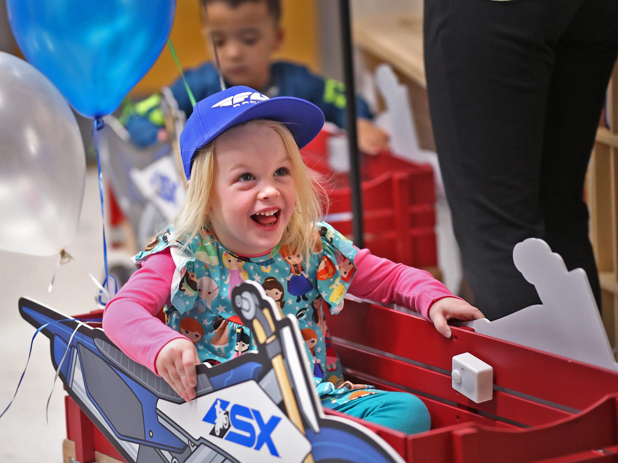 Nola Coleman laughs while getting a wagon ride from Supercross racer Mike Alessi visiting with kids at Day Early Learning Center, Thursday, March 14, 2019.  Alessi provided Supercross rider jerseys and hats for the kids and gave wagon rides, on a break before the upcoming Supercross race.