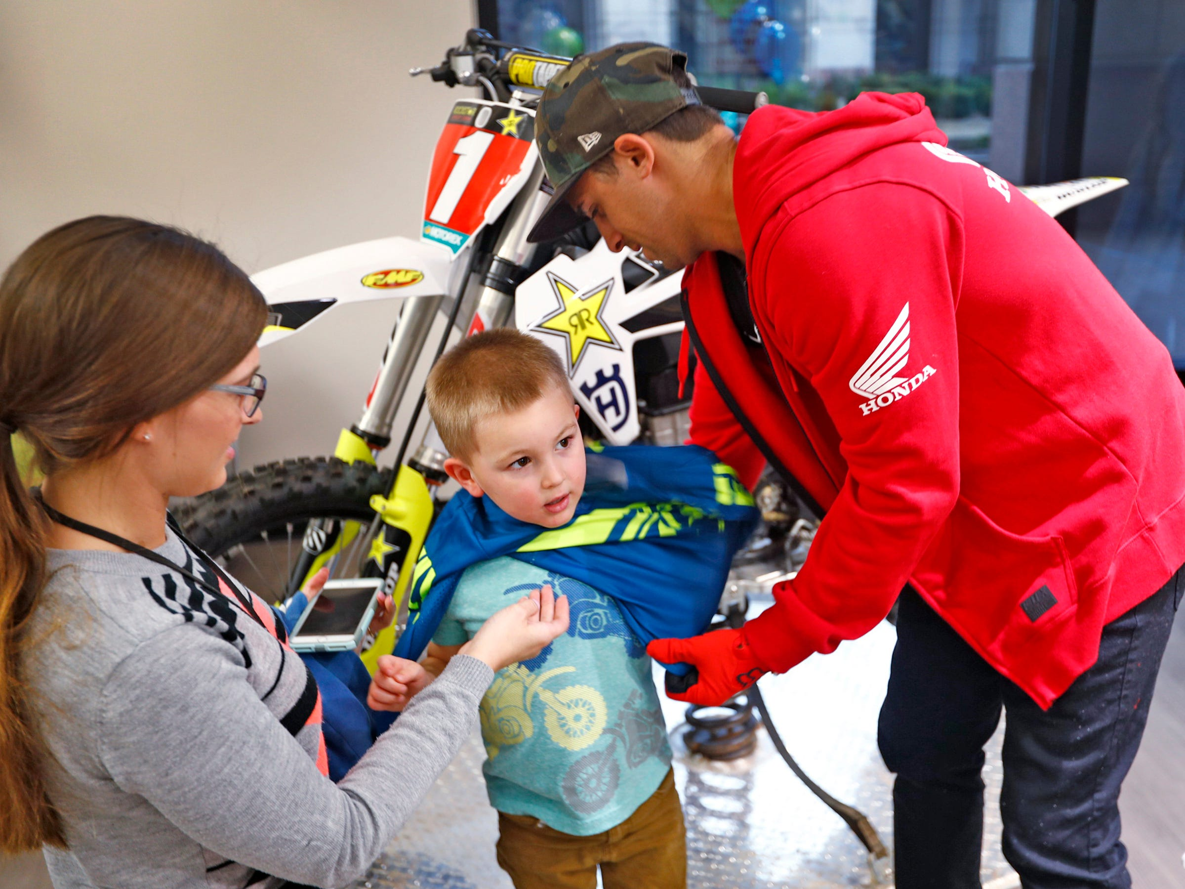 Savanna Hickle, left, helps Supercross racer Mike Alessi, right, put a jersey on her son Jaxson Bare as Alessi visits with kids at Day Early Learning Center, Thursday, March 14, 2019.  Alessi provided Supercross rider jerseys and hats for the kids and gave wagon rides, on a break before the upcoming Supercross race.