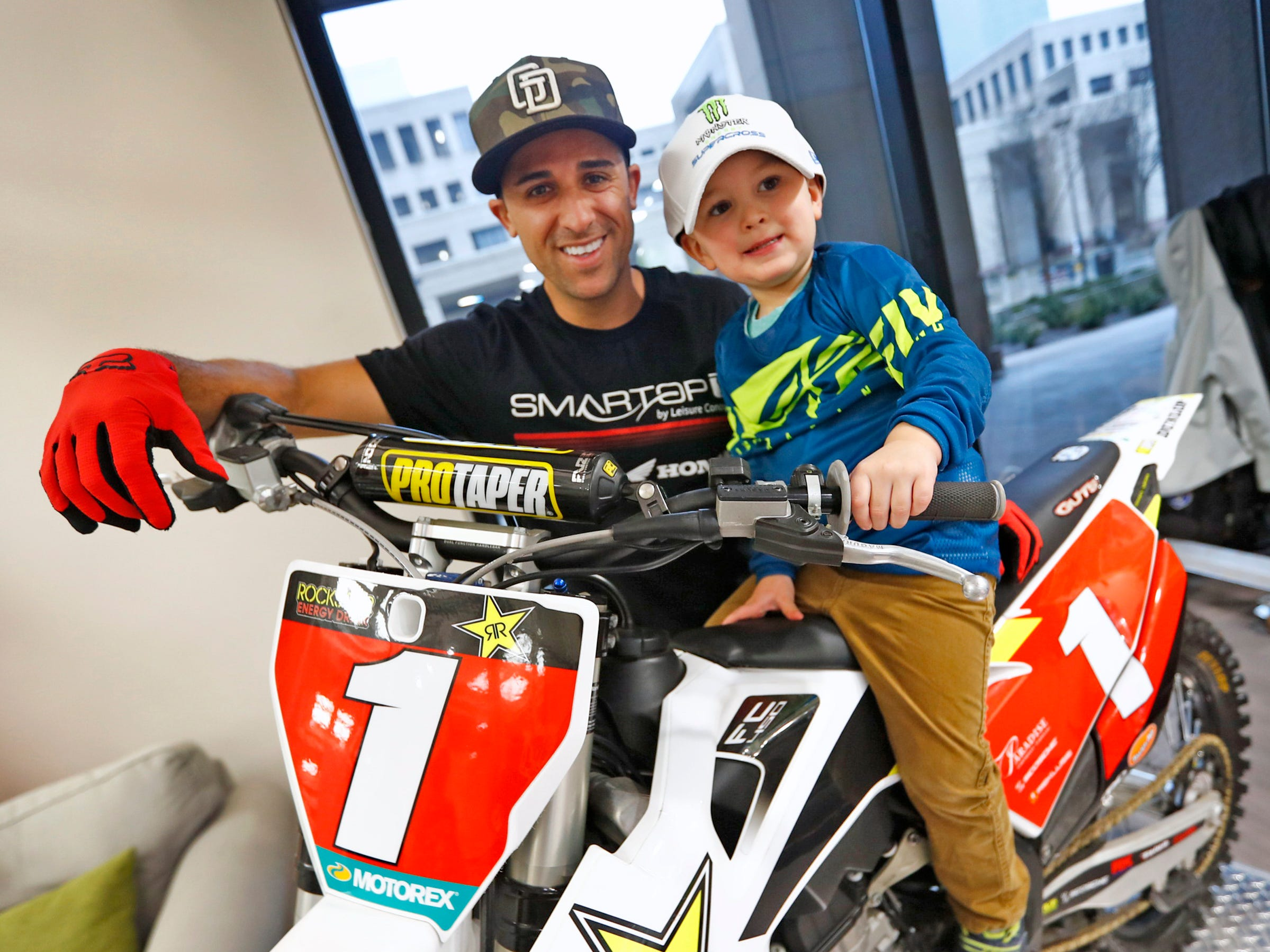 Supercross racer Mike Alessi, left, poses with Jaxson Bare trying out a Superercross simulator, as Alessi visits with kids at Day Early Learning Center, Thursday, March 14, 2019.  Alessi provided Supercross rider jerseys and hats for the kids and gave wagon rides, on a break before the upcoming Supercross race.