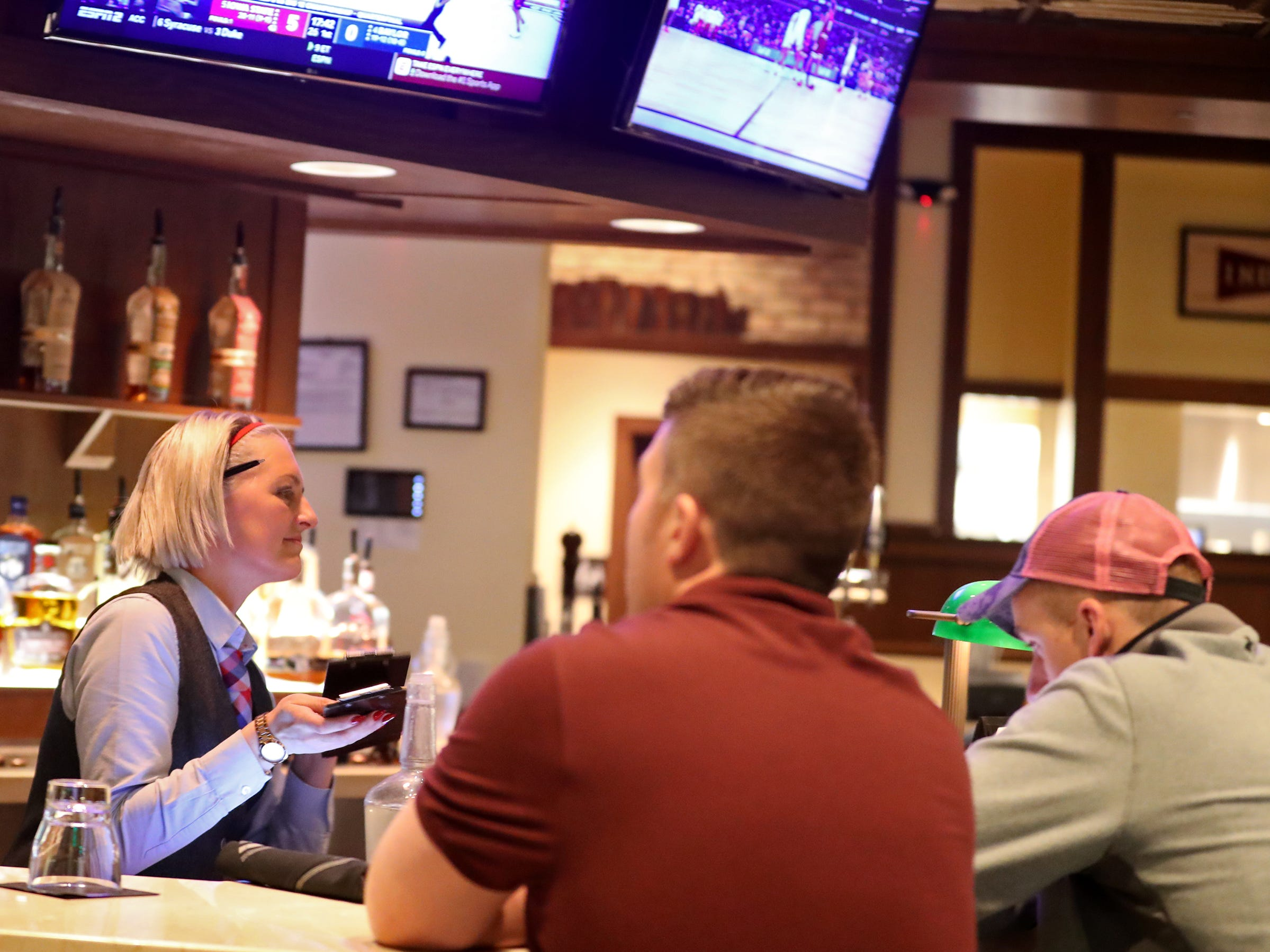 Roxanne Green helps customers at the bar at Burger Study, Thursday, March 14, 2019.  The restaurant uses Snapshyft to help supplement their staffing during peak times.