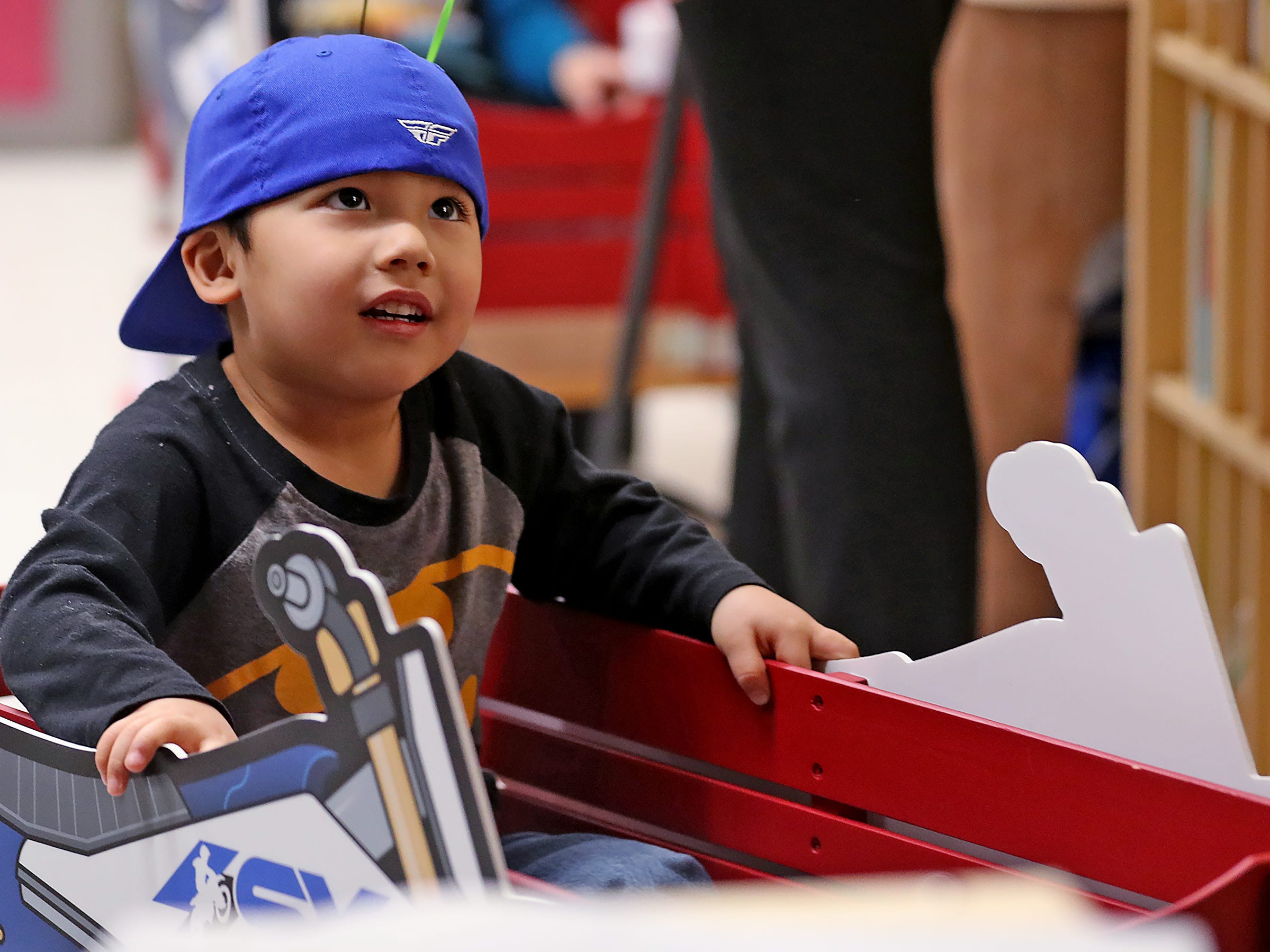 Leo Nguyen gets a wagon ride from Supercross racer Mike Alessi visiting with kids at Day Early Learning Center, Thursday, March 14, 2019.  Alessi provided Supercross rider jerseys and hats for the kids and gave wagon rides, on a break before the upcoming Supercross race.