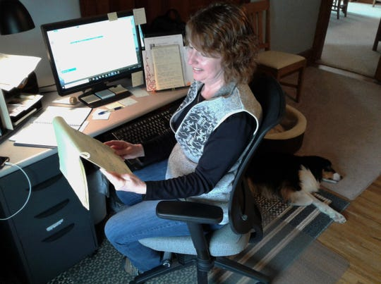 Melinda Wichmann says organizing stories for her newspapers with notes on a legal pad may contrast the high-tech electronic side of her job, but it works. Her Australian Shepherd named Banner rests nearby in her tidy home office.