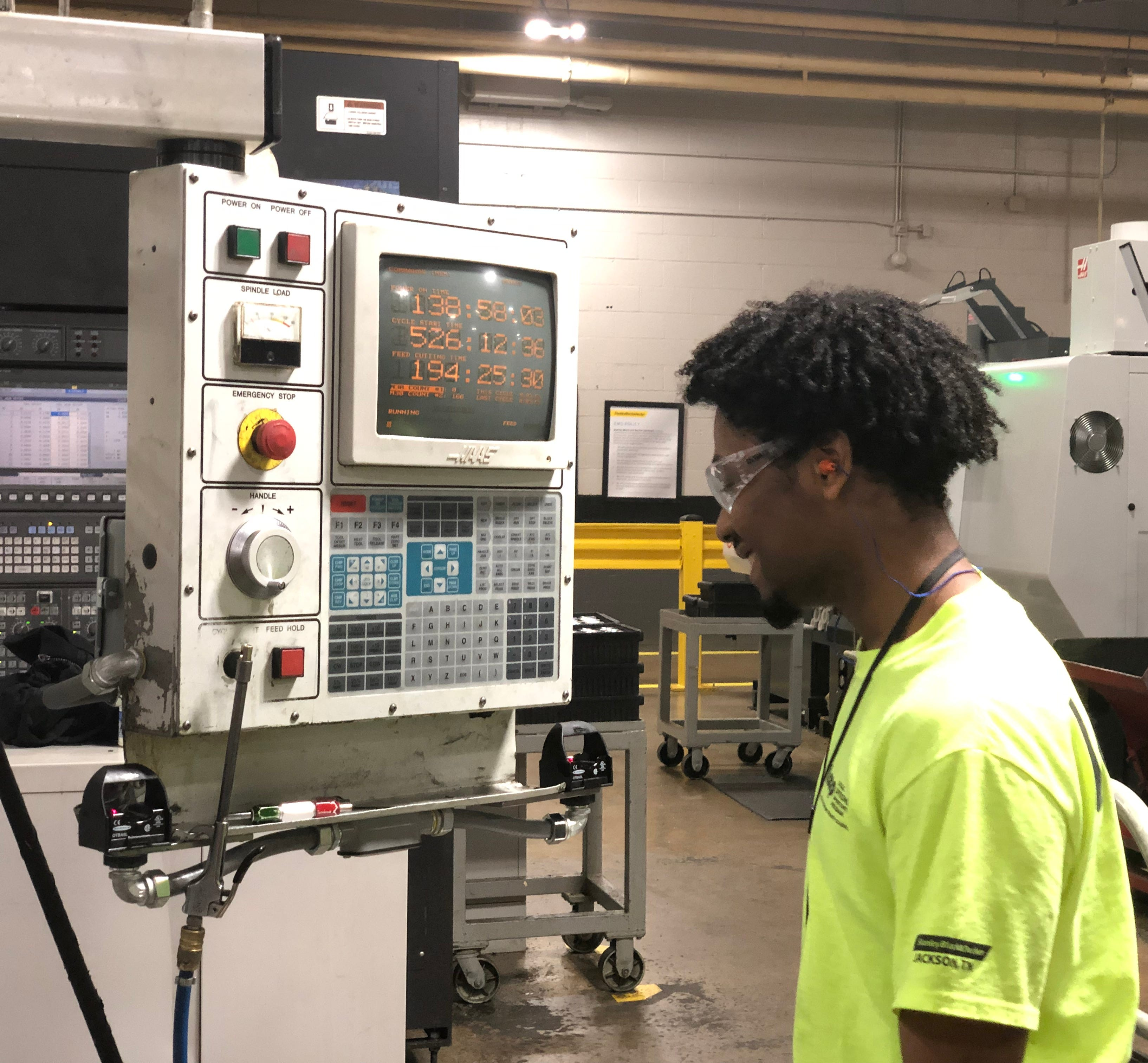 Cameron Walker smiles after completing a task on the mill machine at Stanley Black & Decker.
