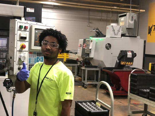 Cameron Walker, a senior at North Side High School, gives a thumb up while wearing his required protective gloves, ear plugs and safety goggles.