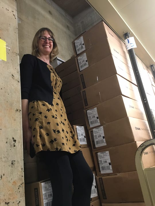 """Coordinator for the Friends of the Knox County Public Library Kristen Faerber laughs as she scales the tallest stack of books, sorted and ready for the annual sale. """"This one is two stories high!"""" she says."""