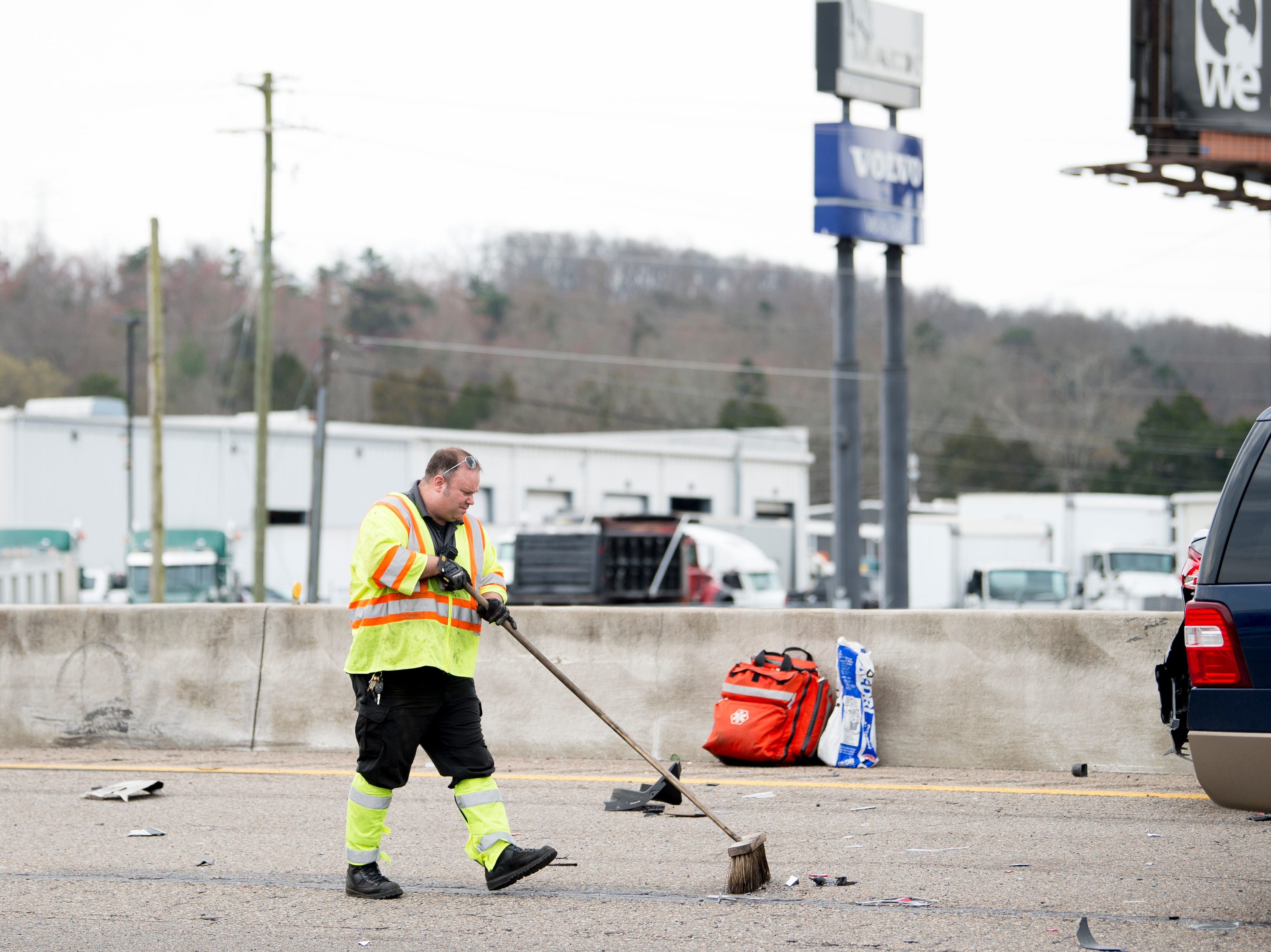 A first responder sweeps up debris at the scene of a multiple vehicle pileup on I-75 northbound near the Callahan Drive exit in Knoxville, Tennessee on Thursday, March 14, 2019. The crash sent several to the hospital and backed up traffic to the I-640 interchange.