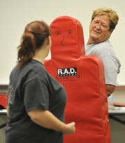 In this 2011 file photo, Nancee Heath holds a bag so Tera Kleinfelter can kick it during a RAD, Rape Aggression Defense systems, class at the West Lafayette Police Department.