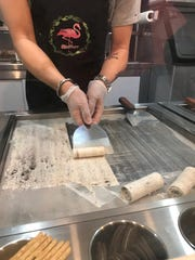 """An employee of Miss Sugar works to roll the """"Cookie Monster"""" ice cream, consisting of vanilla ice cream and crushed Oreo cookies."""